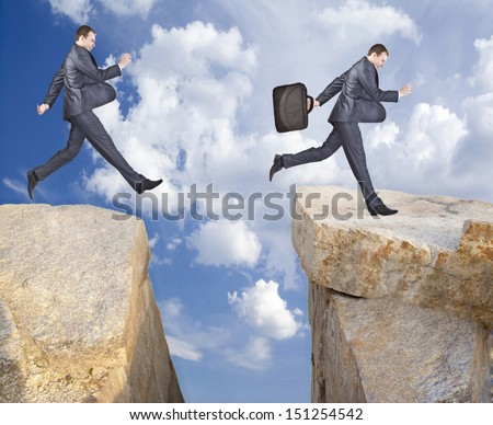 Business young Man jumping over mountains Copy Space for inscription symbol of overcoming obstacles effort new level from one edge abyss empty and on other with case  symbol good luck acquisitions - stock photo