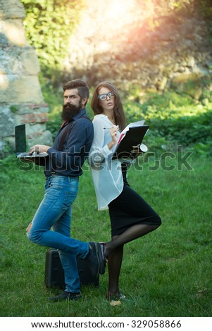Business young pair of slim woman and man with long lush black beard with office devices of laptop glasses mobile phone paper folder and standing outdoor on green grass, vertical photo - stock photo