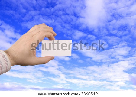 businesskort in the hand, towards the blue sky - stock photo