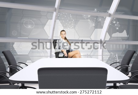 Businesslady sitting half-turned at table and looking at camera on abstract background