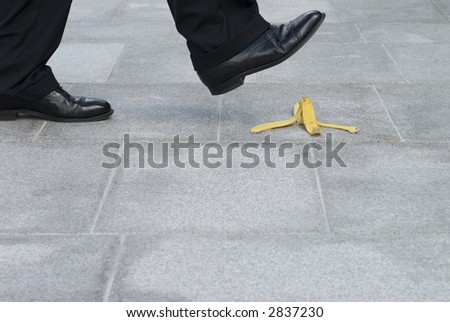Businessman about to have an accident by slipping on a banana skin or peel.  Copyspace. - stock photo