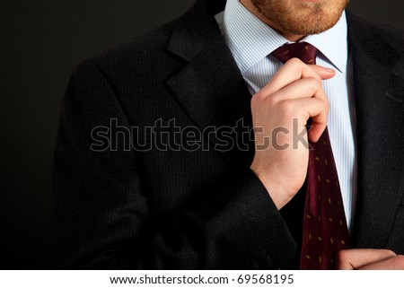 Businessman adjusting his look on a dark background - stock photo