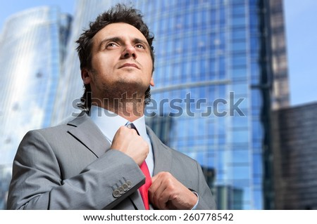 Businessman adjusting his necktie - stock photo