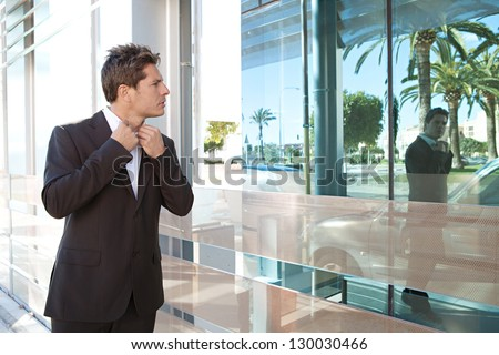 Businessman adjusting his shirt neck collar on a modern office building glass reflection as he walks through the financial city district. - stock photo