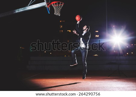 Businessman after hard working day plays basketball. Slam Dunk. - stock photo
