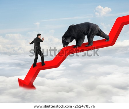 Businessman against black bear on red arrow downward trend line with sky cloudscape background. Fight back bearish market concept. - stock photo