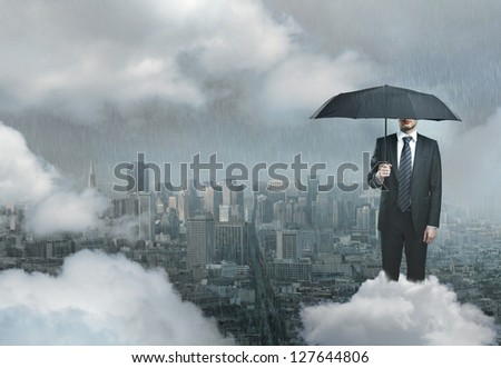 businessman an on cloud with umbrella against background of city