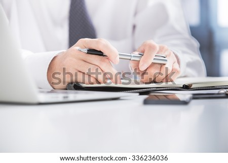 Businessman analyzing data in office - stock photo