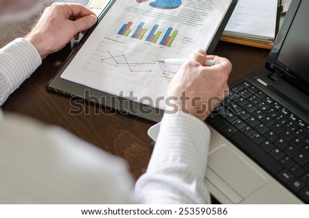 Businessman analyzing economic graphs at office - stock photo