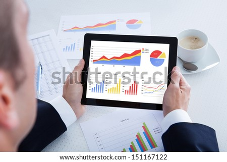 Businessman Analyzing Graph On Digital Tablet In Office - stock photo