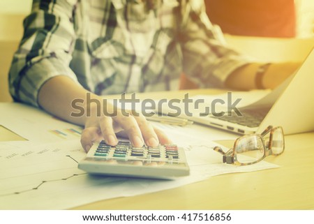 Businessman analyzing investment charts with calculator laptop. Accounting and technology in office.Business people using laptop at office,Analyze plans.selective focus,vintage colorâ?¨ - stock photo