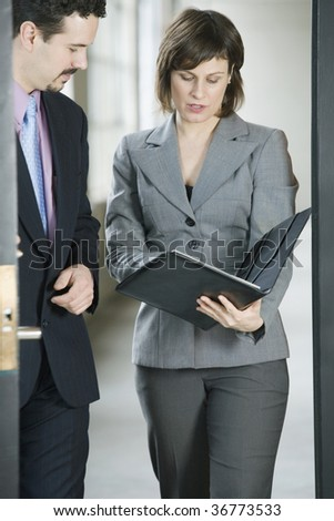 Businessman and a businesswoman examining a document - stock photo