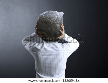 businessman and a stone  on his head - stock photo