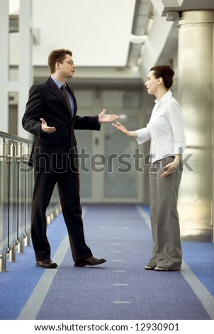 Businessman and busiensswoman having argument in modern office corridor - stock photo