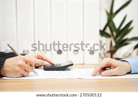 businessman and businesswoman are analyzing financial numbers on document - stock photo