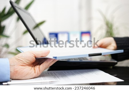 businessman and businesswoman are exchanging document or contract - stock photo