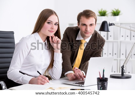 Businessman and businesswoman at computer together, looking in front, office at background. Concept of cooperation. - stock photo