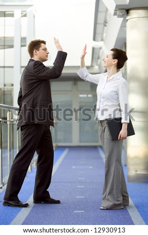 Businessman and businesswoman celebrating success by doing the high-five - stock photo