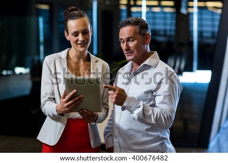 Businessman and businesswoman discuss using digital tablet in the office - stock photo