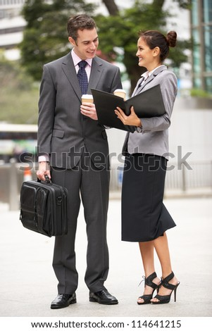 Businessman And Businesswoman Discussing Document In Street Holding Takeaway Coffee