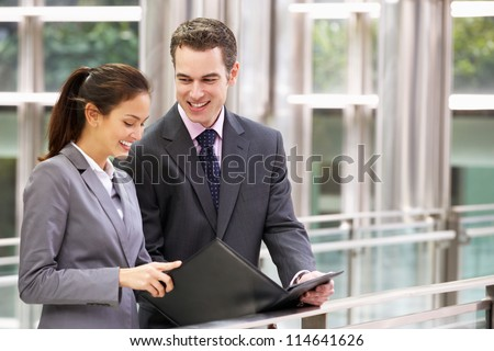 Businessman And Businesswoman Discussing Document Outside Office - stock photo