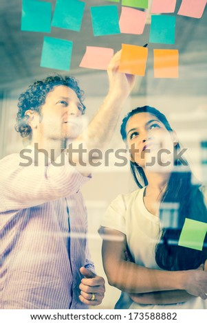 Businessman and businesswoman discussing over adhesive notes on glass wall in office - stock photo