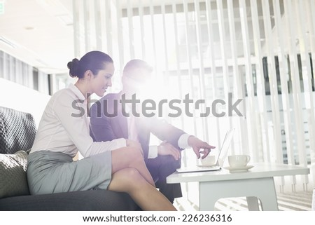 Businessman and businesswoman discussing over laptop in office - stock photo