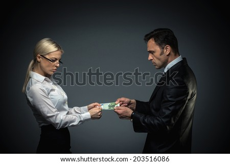 Businessman and businesswoman divide money - stock photo