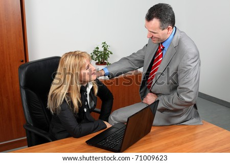 Businessman and businesswoman flirting in the office. - stock photo
