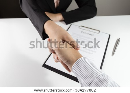Businessman and businesswoman handshake over the  contact document. - stock photo