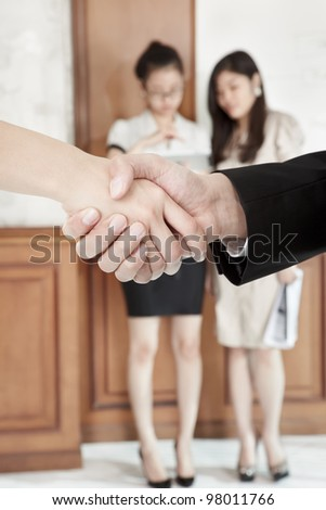 Businessman and businesswoman handshaking in the office with other people o background - stock photo