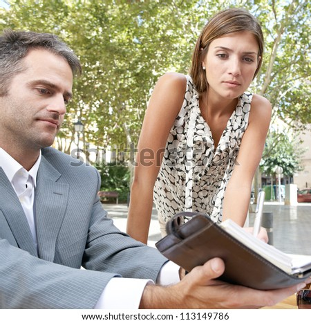 Businessman and businesswoman having a meeting in a coffee shop terrace outdoors. - stock photo