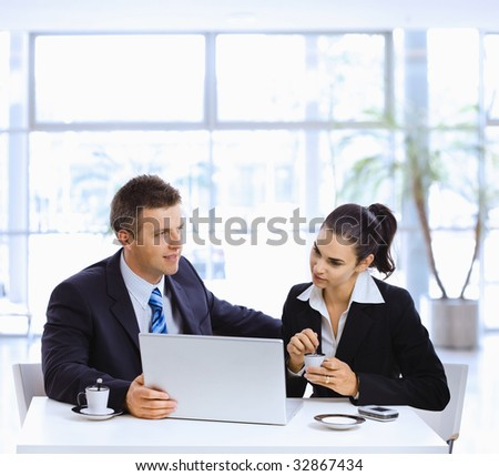 Businessman and businesswoman having a meeting in office lobby, drinking coffee.