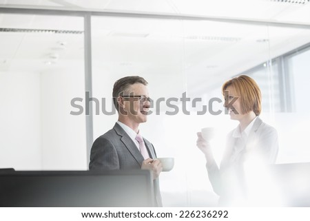 Businessman and businesswoman having coffee in office