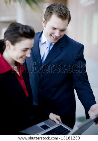 businessman and businesswoman in formal wear looking down at laptop screen - stock photo