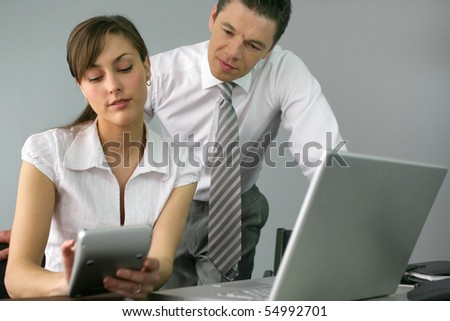 Businessman and businesswoman in front of a laptop computer - stock photo