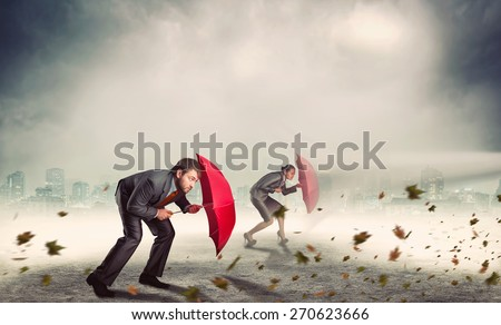 Businessman and businesswoman in storm - stock photo