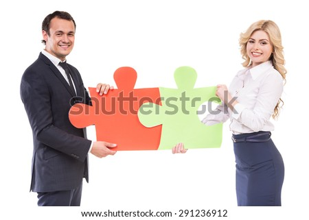 Businessman and businesswoman joining jigsaw pieces of puzzle. Business strategy concept. - stock photo
