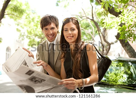 Businessman and businesswoman leaning together on a parked car and sharing a newspaper in a tree aligned street in a classic city, smiling at the camera. - stock photo