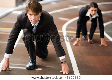 Businessman and businesswoman lined up getting ready for race in business - stock photo