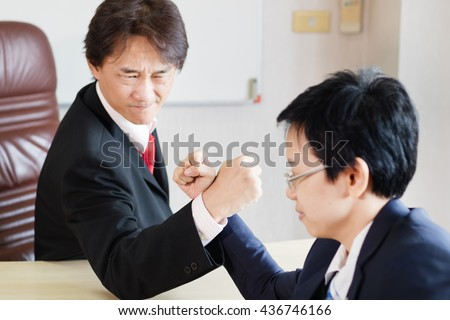 Businessman and businesswoman looking at each other seriously while doing arm wrestling /selective focus on hand - stock photo