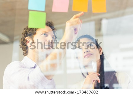 Businessman and businesswoman reading adhesive notes on glass wall in office - stock photo