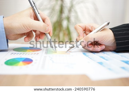 businessman and businesswoman reviewing the analysis of the company's operations - stock photo