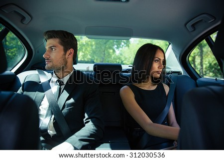 Businessman and businesswoman riding on back seat in luxury car - stock photo