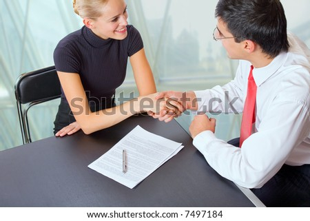 Businessman and businesswoman shaking hands at office