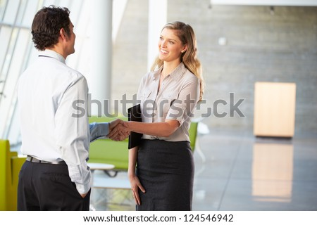 Businessman And Businesswoman Shaking Hands In Office - stock photo