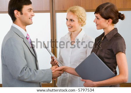 Businessman and businesswoman shaking hands in the room - stock photo