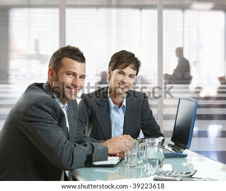 Businessman and businesswoman sitting at desk in office, using laptop computer, smiling. - stock photo