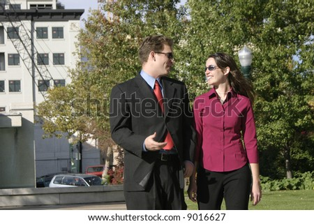 businessman and businesswoman standing and talking face to face smiling