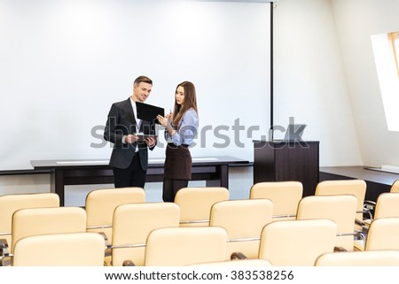 Businessman and businesswoman standing and working in empty meeting hall - stock photo